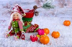 Weihnachtsszene mit Elfe, Weihnachtssocken, Tangerinen und Geschenken Stockbild