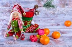 Weihnachtsszene mit Elfe, Weihnachtssocken, Tangerinen und Geschenken Stockfotos