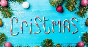 Weihnachtstabelle mit Fichtenzweigen und, Glückwünsche von den Karamellstöcken Lizenzfreies Stockbild
