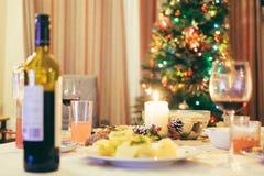 Weihnachtstabelle mit Wein, Lebensmittel, Kerze und Weihnachtsbaum im Hintergrund Mittlerer Fokus Lizenzfreie Stockfotos