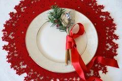 Weihnachtstabellen-Gedeck mit Tischbesteck, Niederlassung des Weihnachtsbaums und rotes Band auf rotem woolen und weißem Hintergr stockbilder