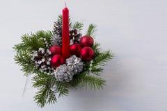 Weihnachtstabellenmittelstück mit Kegel der roten Kerze und der silbernen Kiefer Stockfotografie