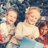 Weihnachtstag in der Familie, die Kinder, die Geschenke auspacken Lizenzfreie Stockfotografie