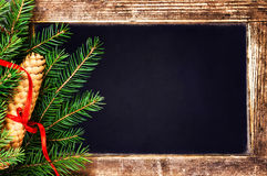 Weihnachtstannen-Baumast und Kiefernkegel auf Weinlese-Tafel Stockbild