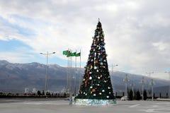 Weihnachtstannenbaum auf einem Quadrat von Ashgabad und von Bergen als zurück Stockbilder