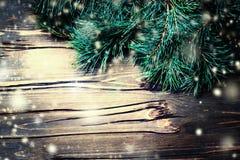 Weihnachtstannenbaum auf hölzernem Brett mit Schneeflocken in der Weinlese Lizenzfreies Stockfoto