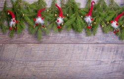 Weihnachtstannenbaum auf hölzernem Hintergrund Weihnachtsgnomdekor mit Sankt-Hut Stockbilder