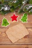 Weihnachtstannenbaum mit Schnee und Feiertagsdekor auf rustikalem hölzernem Stockfotografie