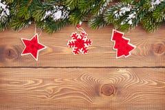 Weihnachtstannenbaum mit Schnee und Feiertagsdekor auf rustikalem hölzernem Stockbild