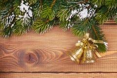 Weihnachtstannenbaum mit Schnee und Feiertagsdekor auf rustikalem hölzernem Lizenzfreie Stockfotos