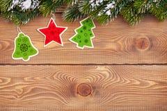 Weihnachtstannenbaum mit Schnee und Feiertagsdekor auf rustikalem hölzernem Stockfoto