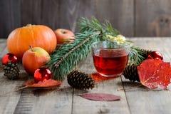 Weihnachtstannenbaumast und Kräutertee mit Spielwaren, Kürbisen, Äpfeln und Herbstlaub Stockfotografie