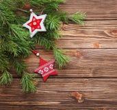Weihnachtstannenbaumaste mit hölzernen Sternen auf einem hölzernen backgr Stockbild