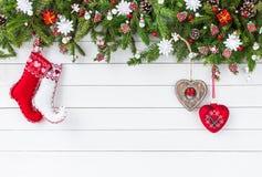 Weihnachtstannenbaumaste, Weihnachtssocken auf weißem Hintergrund des hölzernen Brettes Draufsicht, Kopienraum Lizenzfreie Stockfotografie