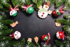 Weihnachtstannenzweige mit Dekorationen auf einem schwarzen Hintergrund Stockbild