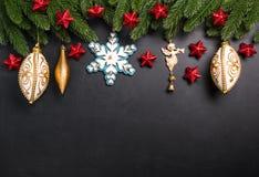Weihnachtstannenzweige mit Dekorationen auf einem schwarzen Hintergrund Stockfotografie