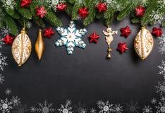 Weihnachtstannenzweige mit Dekorationen auf einem schwarzen Hintergrund Lizenzfreies Stockfoto