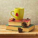 Weihnachtsteebecher auf Büchern mit Dekorationen Stockfotos
