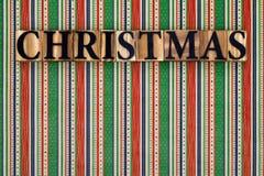 Weihnachtstext auf gestreiftem Hintergrund Stockfotografie