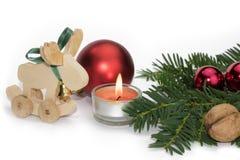 Weihnachtstierfigur mit Kerze und roten Bällen Stockfotografie