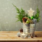 Weihnachtstischschmuck mit Bällen und Kiefernmais über Unschärfehintergrund Stockfotografie