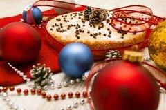 Weihnachtstorte verziert mit dem Stechpalmenzweig und -bällen im festlichen Satz Stockfotografie