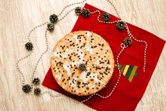 Weihnachtstorte verziert mit dem Stechpalmenzweig und -bällen im festlichen Satz Lizenzfreies Stockfoto