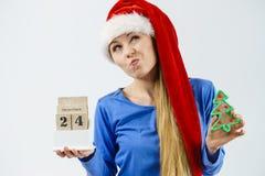 Weihnachtsverwirrte Frau, die Kalender hält Lizenzfreie Stockfotos