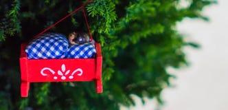 Weihnachtsverzierung eines Babys in einer roten Wiege, die am Baum hängt Lizenzfreies Stockfoto