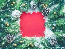 Weihnachtsverzierung mit Tannenbaum, Kiefernniederlassung, Schnee und Hintergrund der roten Karte Lizenzfreies Stockfoto