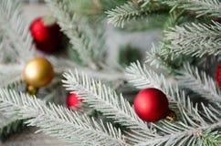 Weihnachtsverzierungen auf Fichtenzweig mit Schnee Stockbild