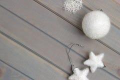 Weihnachtsverzierungen im Weiß auf einem hellgrauen hölzernen Hintergrund Neues Jahr ` s Zubehör Ansicht von oben Lizenzfreie Stockbilder