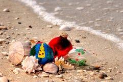 Weihnachtsverzierungen und -oberteile auf einem sandigen Strand mit einem Welle alon stockbilder