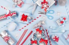 Weihnachtsvorbereitungen - festliche verschiedene Geschenkboxen in der roten, blauen und metallischen Farbe mit Seidenbändern, We stockfotografie