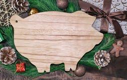 Weihnachtsvorbereitungen, Schneidebrett in Form von Schweinen, Tannenzweige, Kegel und Dekorationen Neues Jahr des Schweins auf d stock abbildung
