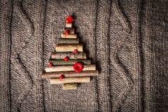 Weihnachtswarmer gestrickter Hintergrund mit den Baumdekorationen des neuen Jahres gemacht von den Stöcken Weinleseweihnachtskart Stockfotografie