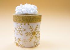Weihnachtsweiße Geschenkbox mit dem goldenen Funkelnmuster, verziert mit einem weißen Bogen, eine romantische Atmosphäre schaffen stockfotografie