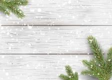 Weihnachtsweißer hölzerner Hintergrund mit Feiertagstannenbaumasten, Kiefernkegel und fallendem glänzendem Schnee Flache Lage, Dr Lizenzfreies Stockbild
