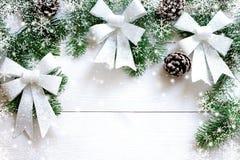 Weihnachtsweißer hölzerner Hintergrund mit Tannenzweigen und Bogen Lizenzfreies Stockbild
