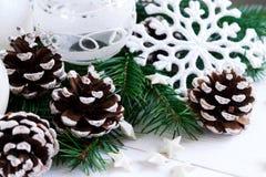 Weihnachtsweißer hölzerner Hintergrund mit Tannenzweigen und Schneeflocken Stockbilder