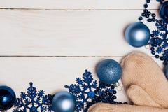Weihnachtsweißer hölzerner Hintergrund von blauen Dekorationen und von Handschuhen, Draufsicht, Nahaufnahme stockfoto