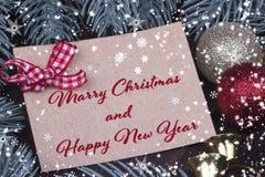 Weihnachtsweihnachtsneujahrsfeiertag-Grußkarte Weihnachtsballglockenbandtannenzweig-Kegelschneeflocken und Text frohe Weihnachten stockfoto
