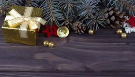 Weihnachtsweihnachtsneujahrsfeiertagdekoration mit der Ballschneeflocken der goldenen Glocke der Geschenkbox natürlichen Tannenzw Stockbild