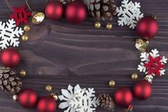 Weihnachtsweihnachtsneujahrsfeiertagdekoration mit der roten natürlichen Tannenzapfen Ballschneeflocken der goldenen Glocke auf d Stockfoto
