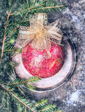 Weihnachtsweinlesedekoration mit rotem Ball, Weihnachtsbaumast mit Schnee Stockfotografie