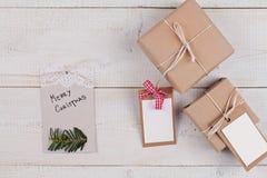 Weihnachtsweinlesegeschenkboxen auf weißer rustikaler Tabelle Weihnachtsgeschenke mit Tags des Kopienraum-freien Raumes Grußkarte Lizenzfreies Stockfoto