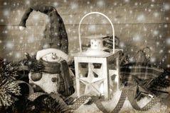 Weihnachtsweinleselaterne im Schnee am hölzernen Hintergrund im Sepia Stockbild