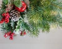Weihnachtswinterdekorationen Weihnachtsgrenze mit Fichtenzweigen im Schnee, Kegel, rote Beeren Stechpalme, roter Apfel Stockfotografie