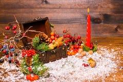 Weihnachtswinterstillleben mit geöffnetem vollem Kasten, Kerze, appl Stockfotografie