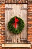 WeihnachtsWreath, hölzerne Blendenverschlüsse, rote Backsteinmauer Stockfoto